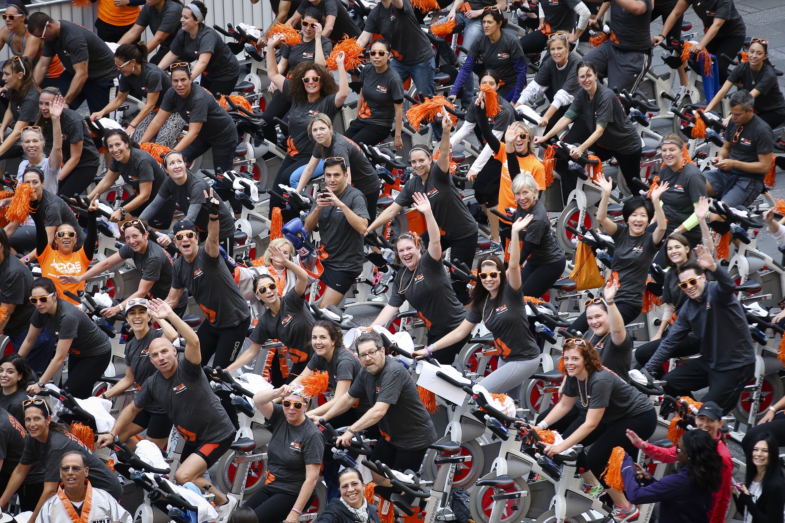 Participants wave during the Cycle for Survival kick-off event as Equinox instructors lead rides in Times Square, Friday, Sept. 19, 2014, in New York. Cycle for Survival is the national movement to beat rare cancers. 100 percent of funds raised go directly to rare cancer research led by Memorial Sloan Kettering Cancer Center. More than $50 million has been raised since its founding in 2007. (John Minchillo/AP Images for Cycle for Survival)